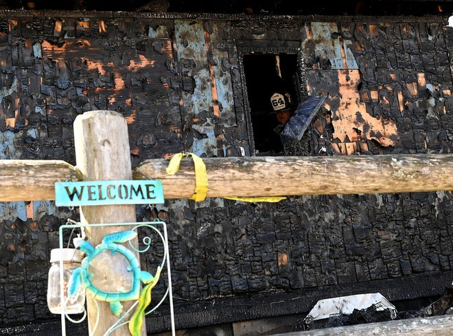 A welcome sign remains intact as a Bellingham firefighter shovels debris from a two-alarm fire Thursday morning that destroyed a home at 63 Box Pond Road on Thursday. Behind the house is Bellingham's Box Pond.