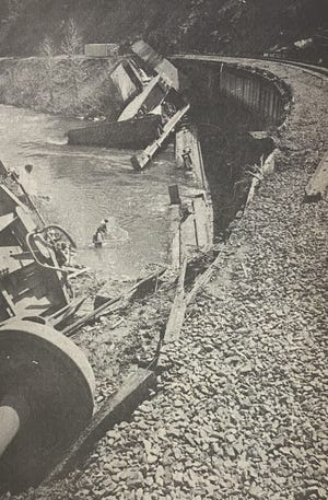 """This photo, from the April 14, 1976 Dunsmuir News archives, was titled, """"Tangle of Steel."""" """"This was the scene after three flat cars containing four vans plunged into the Sacramento River after nine cars jumped the tracks on the Cantara bridge north of Dunsmuir. Guard rails were torn down as the piggybacks plummeted from the tracks, SP salvage workers can be seen in the water and faintly visible on the far side of the river are nets which were placed to catch debris."""""""