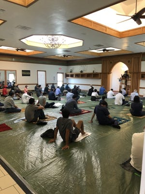 Muslims pray on their personal prayer rugs placed over  a plastic covering as a COVID safety precaution at the Islamic Society of Greater Oklahoma City.