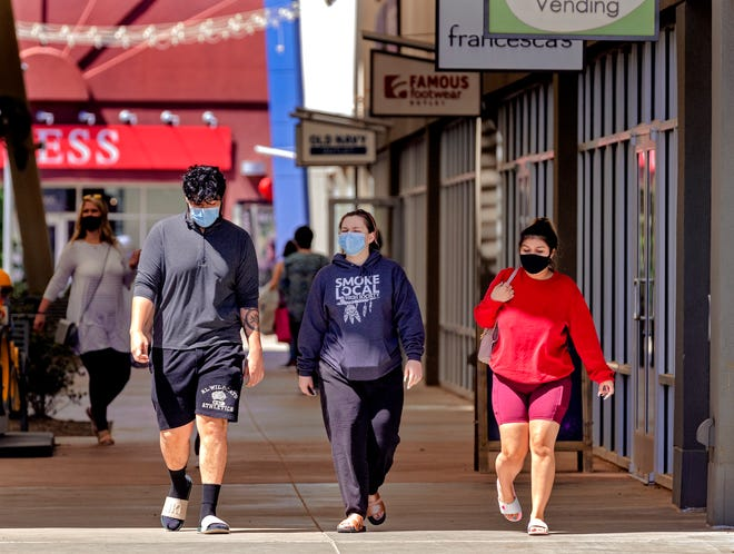 Shoppers wear masks while walking recently at the OKC Outlets mall in Oklahoma City.