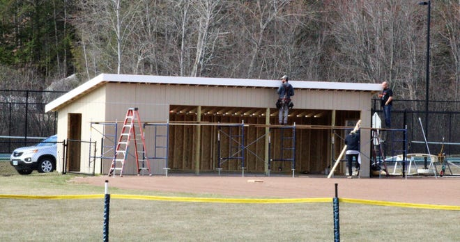 Employees of Seacoast Houseworks work on the dugouts at the new Dover High School softball field Thursday morning. The field will be ready to go in time for Wednesday's home opener against Exeter.
