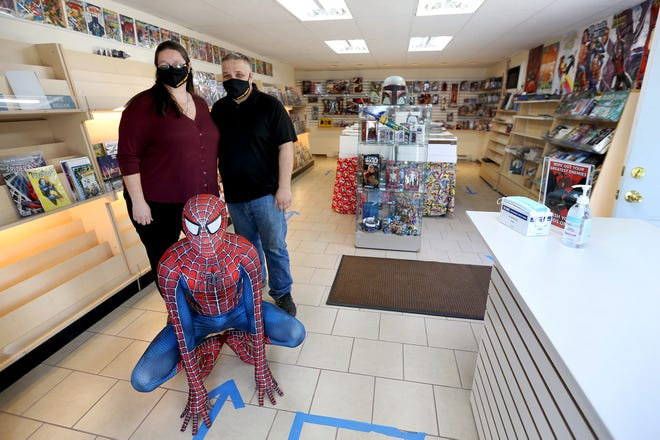 Owners Jessica Lindahl, her husband Jason, and their son, Jason, 16, dressed as Spider-Man, have more than 30,000 comic books in their Khaotic Comics store in Dover