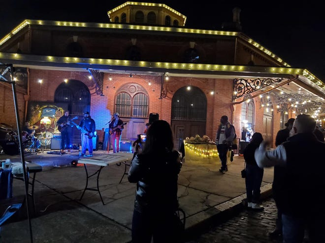 Bank Street Project performs at the 7Moons Artisan Market during Friday for the Arts! with the iconic Farmers Market building as their backdrop in Old Towne Petersburg.