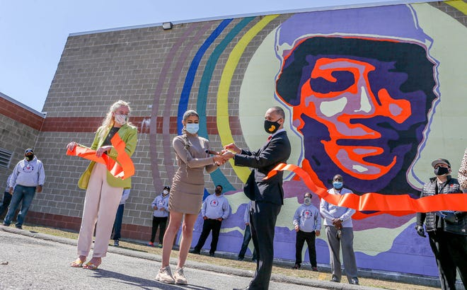 Providence Mayor Jorge Elorza announces the reopening of Providence recreation centers and youth summer employment opportunities Thursday at the Madeline Rogers-Selim Recreation Center. He used the occasion to pay tribute to a new mural of Rogers-Selim, a former rec-center director, painted by Latina artist/activist Ysanel Torres, center. At left is City Councilwoman Katherine Kerwin.
