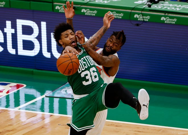 Celtics guard Marcus Smart and New York Knicks forward Reggie Bullock battle for the ball during the fourth quarter Wednesday night at TD Garden.