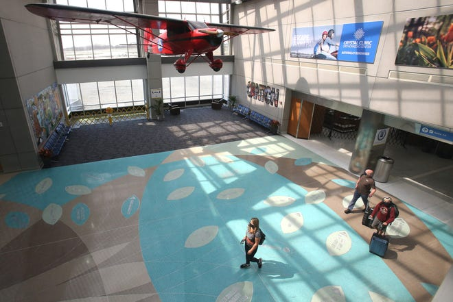 Travelers walk through the atrium at Akron-Canton Airport crossing the new terrazzo floor designed to resemble a Tree of Life. There are 46 leaves recognizing people, places, businesses and events tied to the Canton and Akron communities.