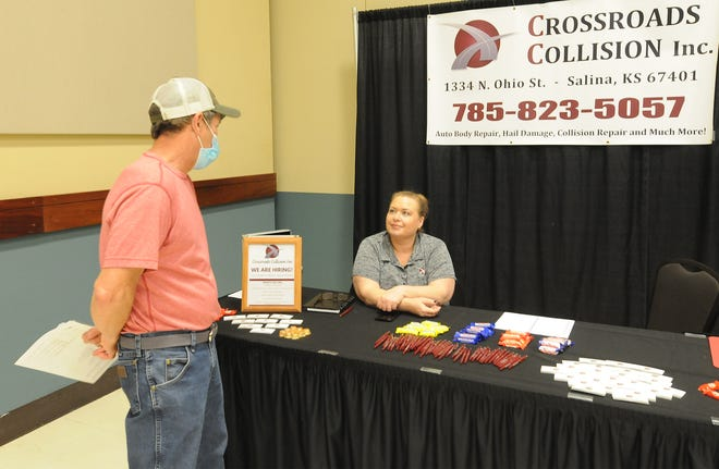 """Randy Carson, of Lindsborg, visits with Heike Anderson at the Crossroads Collision booth during the Salina Area Job Fair in the Great Plains Manufacturing Convention Hall at the Tony's Pizza Events Center on Wednesday evening. """"I work for El Dorado National, and we will be out of a job in a month, so I thought I would come and see what is available,"""" said Carson."""
