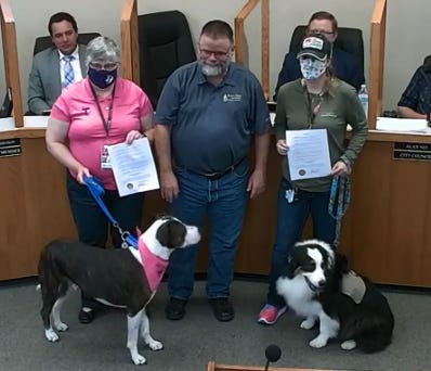 Mayor Doug Svien, center, presents proclamations in honor of National Therapy Animal Day to Jennifer Yeager, left, with PAWS for Nursing at Tarleton State University and Lyndi Hannah, founder of Annie's Therapeutic Companions.