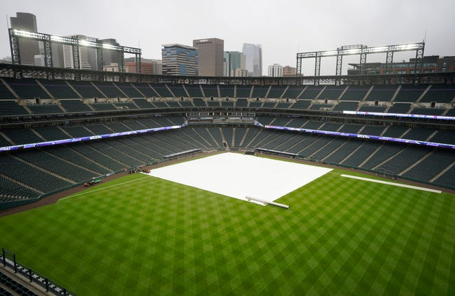 Grounds crew workers pull the tarpulin as a light rain descends on Coors Field Tuesday, April 6, 2021, before the Colorado Rockies host the Arizona Diamondbacks in a baseball game in Denver. Major League Baseball announced that Coors Field will be the venue for the 2021 All Star Game after the Midsummer Classic was moved out of Atlanta because of sweeping changes to voting rights established in the state of Georgia. (AP Photo/David Zalubowski)