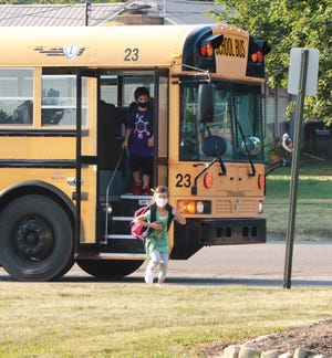 Students exit from a district bus in August at Wall Elementary in Sturgis. The board of education will consider two bus purchases for the 2021-22 school year.