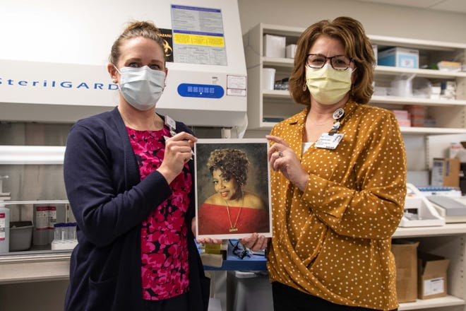 Lab manager Mallory Kennedy, left, and lab director Jennifer Lewis, right, hold up a photograph of Elizabeth Edwards that will be hung in memoriam at the hospital's laboratory entrance. Edwards was the first person in Craven County to die of COVID-19, one year ago.