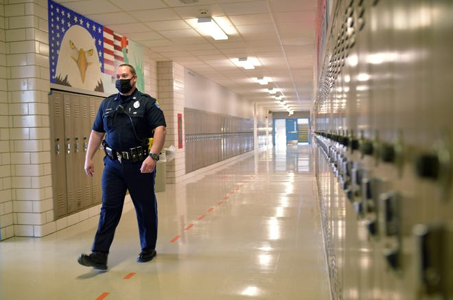 School resource officer Todd Laporte walks down the hall at David Prouty High School Thursday in Spencer.