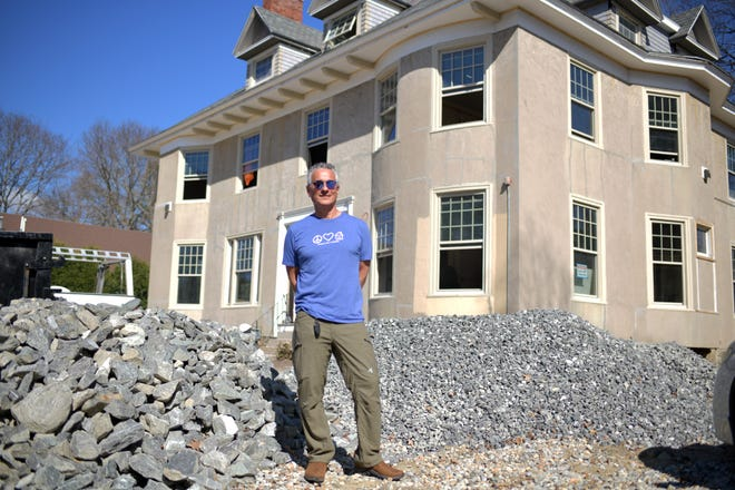 Russ Haims, owner of Hampton Properties LLC, stands near piles of rock for drainage at his Cedar Street property Thursday.