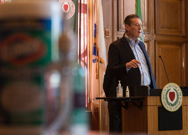 A container of Clorox wipes and a bottle of hand sanitizer sit on a nearby table at City Manager Edward M. Augustus Jr. speaks during the weekly COVID-19 press conference Thursday at City Hall.