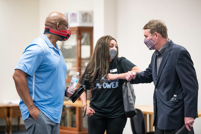 U.S. Sen. Michael Bennett, right, elbow bumps Brandi Adakai while conversing with her and Christopher Hall after a roundtable event at the Boys and Girls Club on Thursday April 8, 2021.