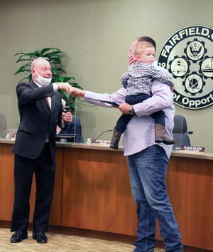 Fairfield Mayor Steve Miller gives resident Kyle Weidner a fist bump after reading a proclamation in his honor for his heroism when a fire broke out at a neighbor's house. Weidner is holding his son Ernie.