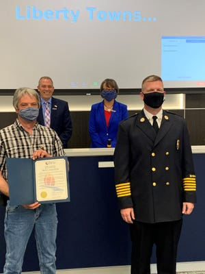 Richard Ross stands with Liberty Township Fire Chief Ethan Klussman after receiving a proclamation from township trustees (back) Tom Farrell and Christine Matacic.