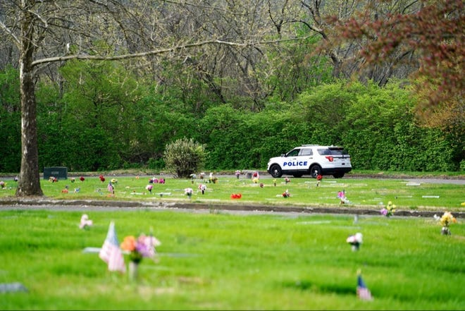 A police car is seen at St. Joseph Cemetery in Cincinnati's West Side, where reports were made about monkeys on the loose overnight.
