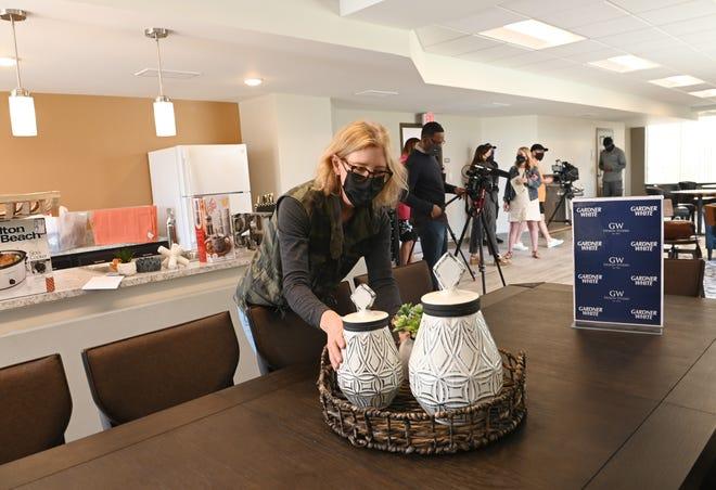 Jean Hershey dari Humble Design of Detroit, meletakkan pot bunga di atas meja di ruang komunitas di apartemen Coolidge Center.