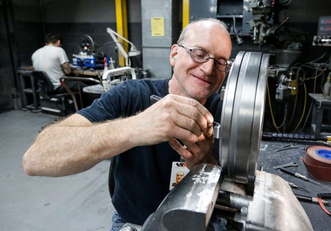 Tim Abler polishes an extrusion die at Mid-States Aluminum in Fond du Lac. Abler hasn't missed a day of work during his 40 years of employment.