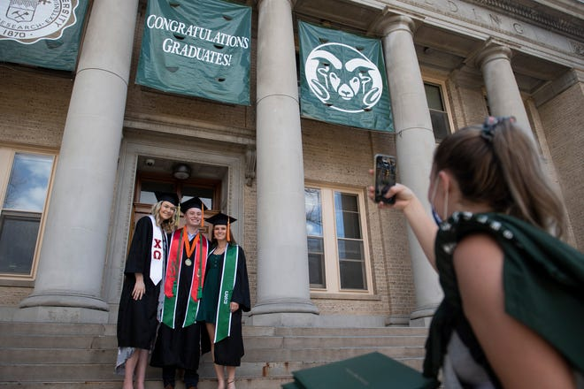 A woman takes a photo of graduates on the steps of the administration building after a ceremonial oval walk for commencement at Colorado State University in Fort Collins, Colo. on Thursday, April 8, 2021.