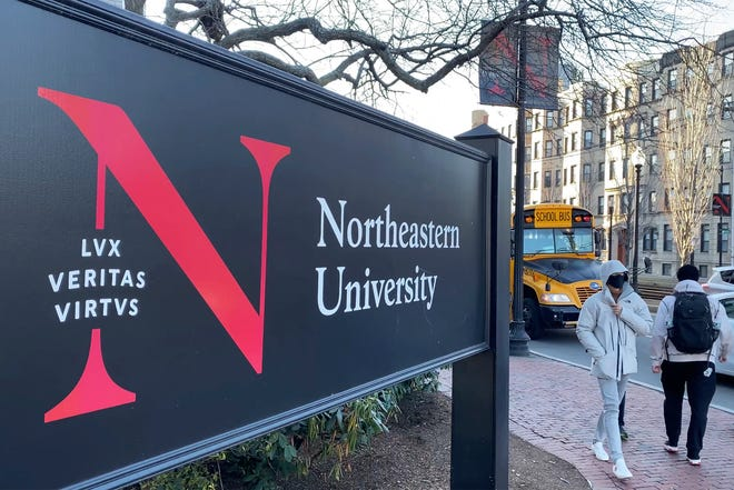FILE - In this Jan. 31, 2019 file photo, pedestrians walk near a Northeastern University sign on the school's campus in Boston. Steve Waithe, 28, of Chicago, a former track and field coach at Northeastern University was arrested, Wednesday, April 7, 2021, and charged with using bogus social media accounts to try to trick female student-athletes into sending him nude photos of themselves, prosecutors said. (AP Photo/Rodrique Ngowi, File)