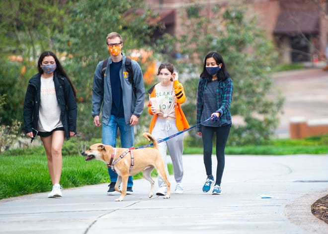 Students and a dog walk together at the University of Tennessee in Knoxville, Tenn., on Thursday, April 8, 2021.