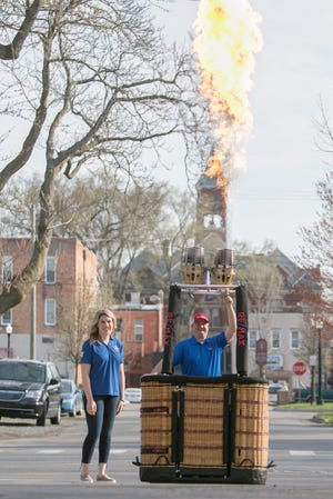 Howell Area Chamber of Commerce president Janelle Best and Re/Max Platinum balloon pilot Dennis Hall fire up the burner on Hall's balloon Thursday, April 8, 2021 as the chamber announced a 2021 Michigan Challenge Balloonfest will take place, but without large group events.