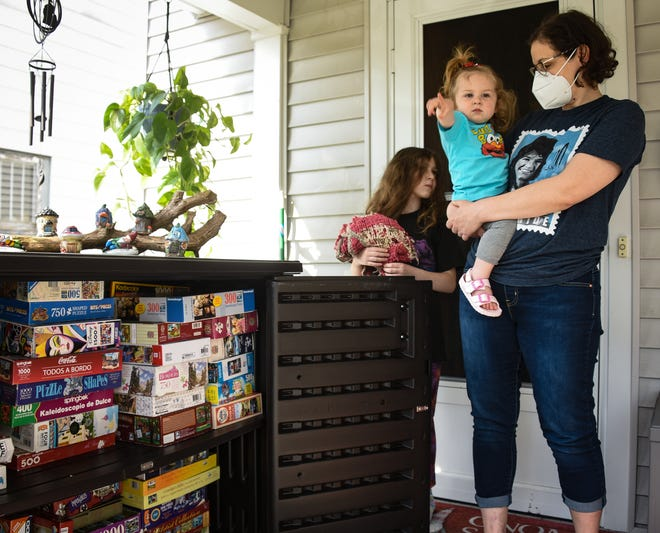 Dmity Palazzola of Lansing, pictured  with daughters Libby, 10, and 18-month-old Birdie, Thursday, April 8, 2021.  During the pandemic, she's set up a free puzzle library on her front porch, where people can leave and take puzzles.