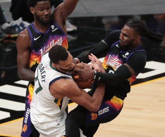 Utah Jazz center Rudy Gobert (27) is tied up by Phoenix Suns forward Jae Crowder (99) during the third quarter in Phoenix April 7, 2021.