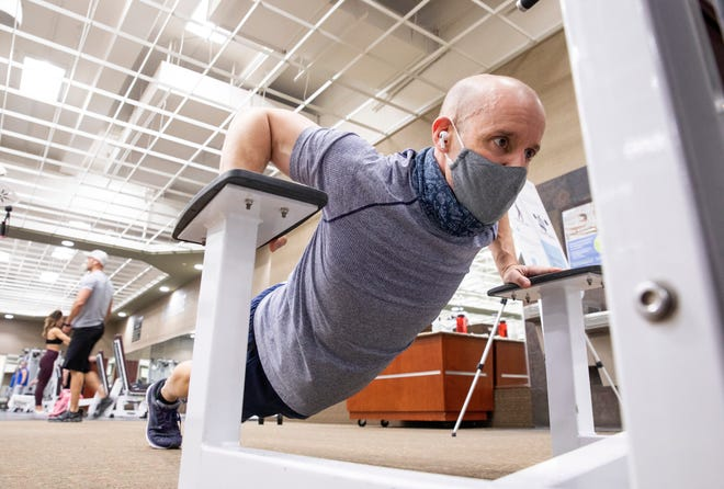 Doctor Joe Gastaldo does push ups as part of his his early morning workout at Life Time Fitness in Dublin, Ohio on March 4, 2021. He wears a gaiter mask while he is working out and makes sure to keep a distance between himself and others when he pulls it down. Gastaldo visits the gym every morning, his exercise helps him deal with the stress of his work as an expert studying Infectious Diseases for OhioHealth.