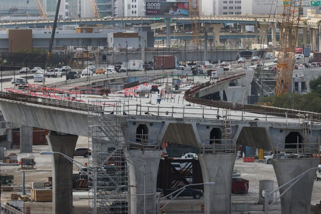 """MIAMI, FLORIDA - MARCH 17: Construction workers build the """"Signature Bridge,"""" replacing and improving a busy highway intersection at I-95 and I-395 on March 17, 2021 in Miami, Florida. The Florida Department of Transportation is building the project in partnership with the Miami-Dade Expressway."""