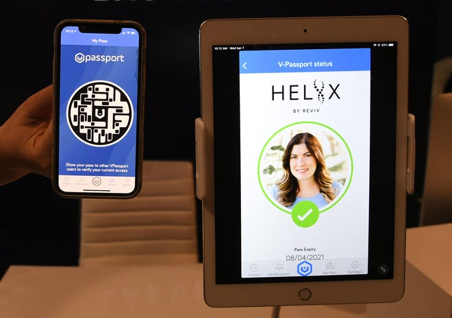 REVIV USA West Coast Operations Manager Kari Armamento uses a cell phone and an iPad to demonstrate the HELIIX Health Passport at REVIV at The Cosmopolitan of Las Vegas on April 7. The app was launched in Las Vegas to help safely bring attendees back to conventions, restaurants and live music and sporting events.