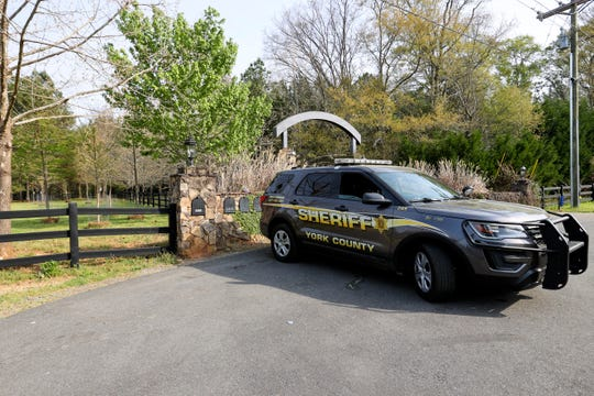 A York County sheriff's deputy is parked outside a residence where multiple people, including a prominent doctor, were fatally shot a day earlier, Thursday, April 8, 2021, in Rock Hill, S.C. A source briefed on the mass killing said the gunman was former NFL player Phillip Adams, who shot himself to death early Thursday.