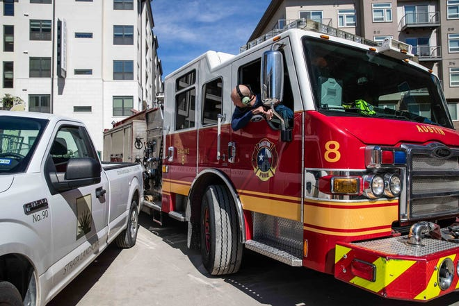 An Austin firefighter drives a fire truck on the narrow streets of Austin in 2019. Prop A would allow the firefighters union or the city to demand binding arbitration if contract talks reach an impasse.