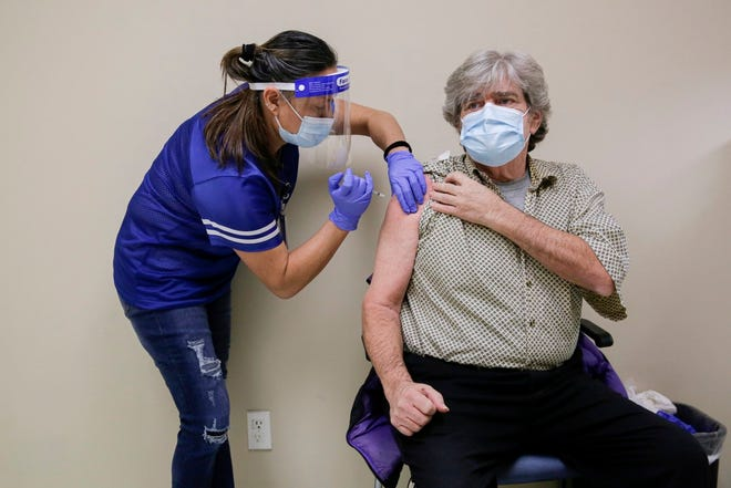 Certified medical assistant Maria Lawlor administers the Moderna coronavirus vaccine to Michael Burns, 62, at Rosewood Zaragosa Health Center in East Austin on Jan. 8, 2021. [BRONTE WITTPENN/AMERICAN-STATESMAN/FILE]