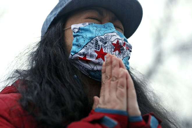 A woman prays during a vigil and rally against Asian hate crimes, March 26 at Chicago's Horner Park. [AP PHOTO/SHAFKAT ANOWAR]