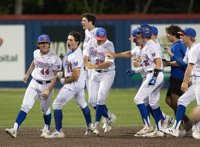 Westlake's Cole May, second from left, is swarmed by his teammates after his hit in the eighth inning accounted for the winning run in a 5-4 win by the Chaps over the Hays Rebels April 8 at Westlake High School.