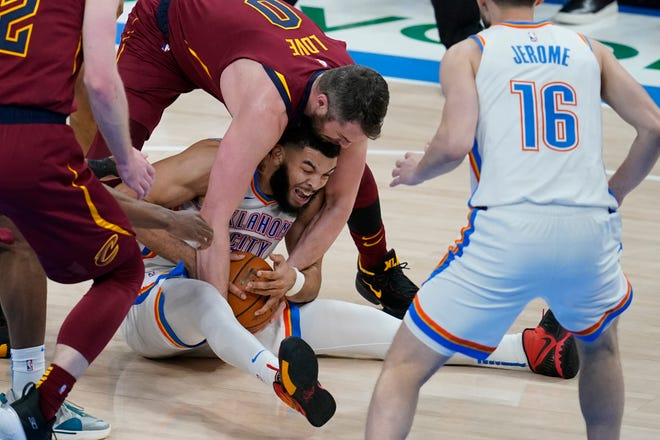 Cleveland Cavaliers forward Kevin Love, top, and Oklahoma City Thunder forward Kenrich Williams try to get control of the ball during the second half of an NBA basketball game Thursday, April 8, 2021, in Oklahoma City. [Sue Ogrocki/Associated Press]