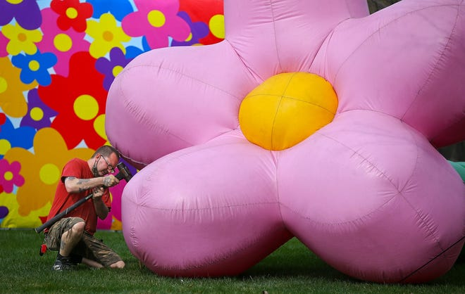 Clyde Taylor of Inflatable Images installs one of the five 20-30 foot long inflatable flowers for the Hope Blooms Ohio display at High Bridge Glens Park, Thursday, April 8, 2021, in Cuyahoga Falls, Ohio. [Jeff Lange/Beacon Journal]