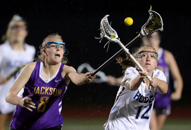 Jackson's Chelsea Debevec, left, and Hudson's Emily Ritenour eye down a loose ball during the second half of a lacrosse game, Thursday, April 8, 2021, in Hudson, Ohio.