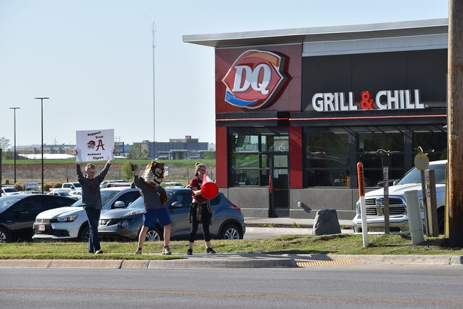 Ardmore High School student athletes wave at passing cars during a fundraiser with the Ardmore Dairy Queen Thursday, April 8, 2021. Over $400 was donated from a portion of the restaurant's sales from Thursday evening.