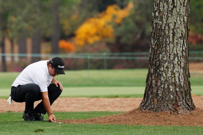 Patrick Reed cleans up behind his ball before hitting his approach on No. 7.