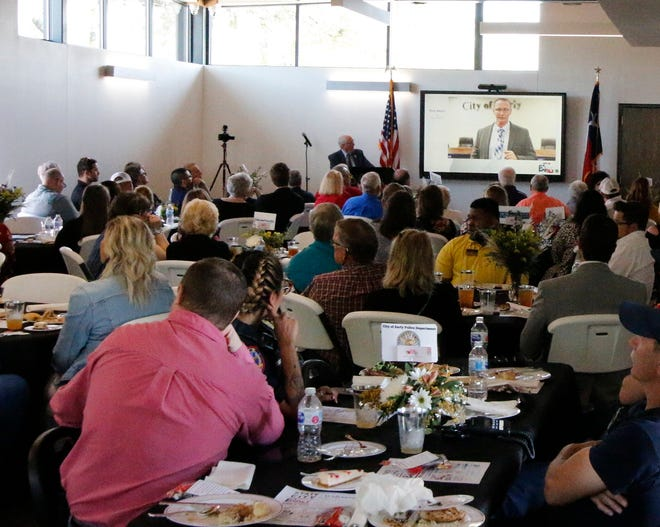 Early Mayor Bob Mangrum watches as City Administrator Tony Aaron speaks on a video during Mangrum's State of the City address Friday.