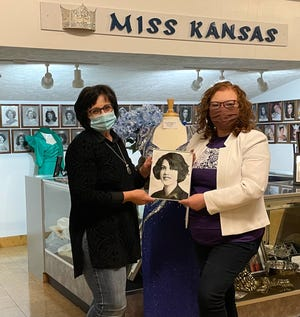 Pratt County Historical Museum curator Charmaine Swanepoel, left, receives a photograph of the first Miss Kansas, Pauline Sayre, from Sierra Marie Bonn. The photo will be added to the Miss Kansas exhibit on the wall of fame highlighting former Miss Kansas'.