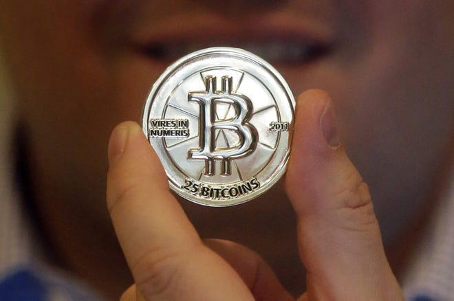 Mike Caldwell, a 35-year-old software engineer, holds a 25 Bitcoin token in 2013 at his shop in Sandy, Utah. Caldwell minted physical versions of bitcoins, cranking out homemade tokens with codes protected by tamper-proof holographic seals, a retro-futuristic kind of prepaid cash. Bitcoin was seeing up to 70,000 transactions each day in 2013 four years after it was invented. (AP FILE)