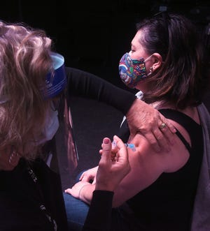 Shelly Sappington, left, a registered nurse with Columbia/Boone County Public Health and Human Services, gives a Moderna COVID-19 vaccine shot to Sara Springer on Friday at The Blue Note. A total of 223 appointments were made for people who work in hospitality or entertainment venues.