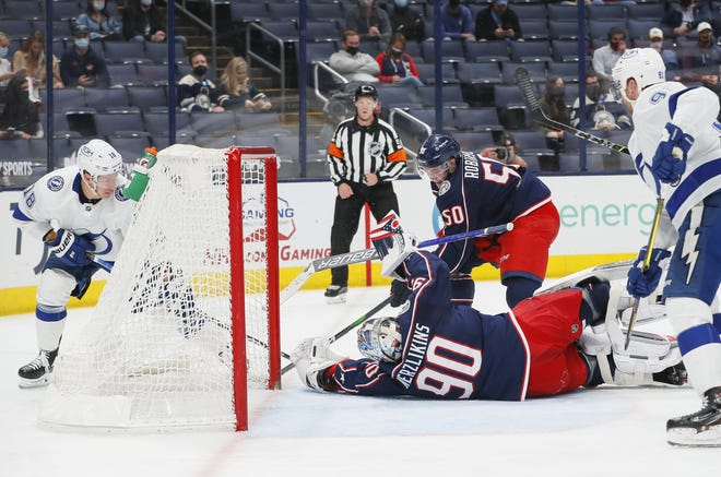 Blue Jackets goaltender Elvis Merzlikins makes a diving stop on a shot from the Lightning's Ondrej Palat, left, during the second period Thursday.