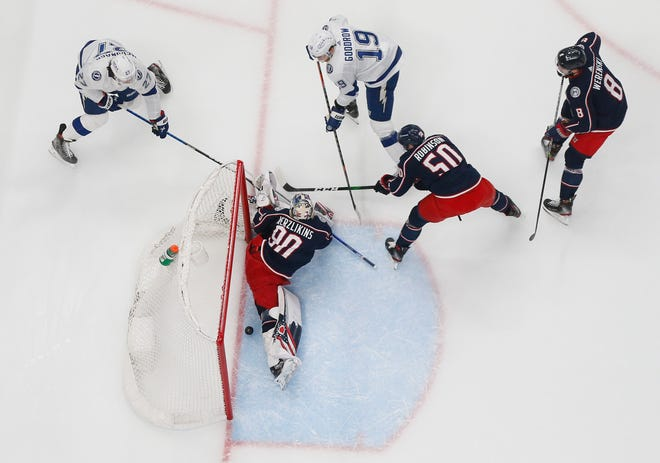 A goal by Tampa Bay Lightning defenseman Ryan McDonagh (27) trickles in behind Columbus Blue Jackets goaltender Elvis Merzlikins (90) in the final second of the first period of the NHL hockey game at Nationwide Arena in Columbus on Thursday, April 8, 2021. Columbus Blue Jackets left wing Eric Robinson (50) and defenseman Zach Werenski (8) defend Tampa Bay Lightning right wing Barclay Goodrow (19).