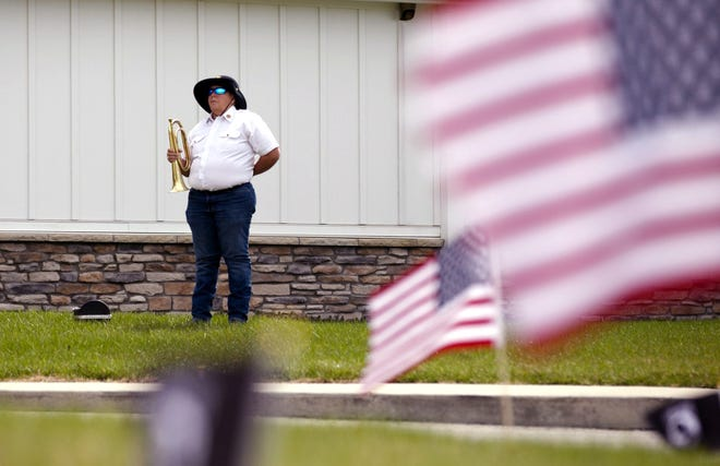 Maria McNicol, of the Mechanicsburg American Legion Post Honor Guard, stands ready to play taps in honor of National Former Prisoners of War Recognition Day Friday at Walnut Crossing Assisted Living Community in Marysville.